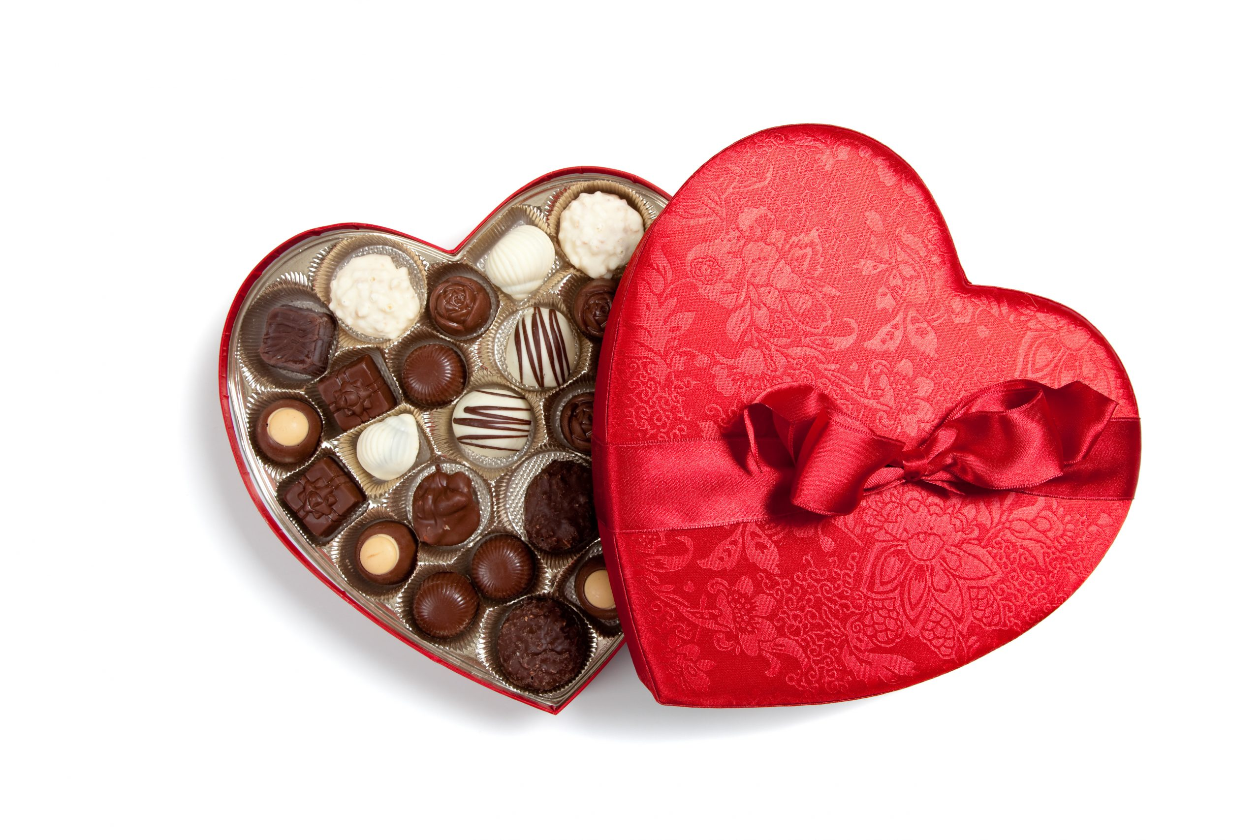 Red heart full of chocolates on white