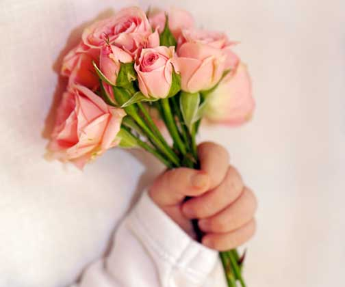 Close-up of newborn baby hand with flowers